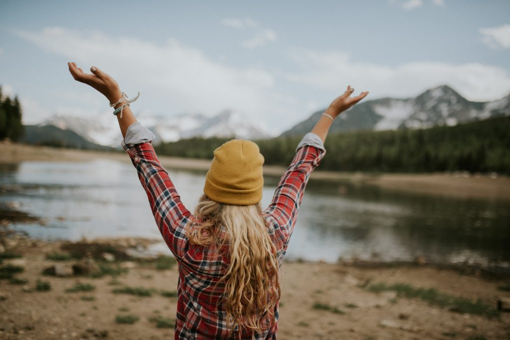 Home business networking hacks Girl her back to us with arms rised high, wearing a mustard colour beanie and red lumberjack shirt. Facing a lake and mountain